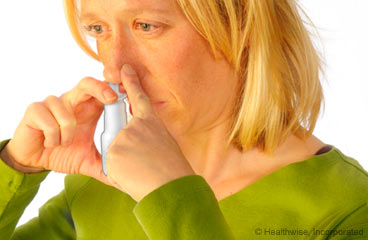 Picture of a woman using nasal spray